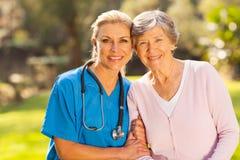 Nurse senior patient. Mid age medical nurse and senior patient outdoors Stock Images