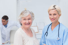 Nurse and senior patient smiling in clinic Stock Photos