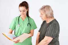 Nurse and senior reading medical file Stock Image