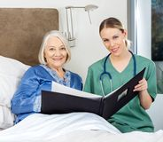 Nurse And Senior Woman With Medical Reports In Royalty Free Stock Image
