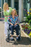 Nurse with Senior Woman in Wheelchair Outdoors Stock Image