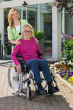 Nurse with Senior Woman in Wheelchair Outdoors Royalty Free Stock Photography