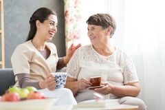 Nurse and senior having fun. Nurse and senior women having fun together while sitting on sofa and drinking tea Royalty Free Stock Image