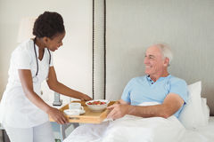 Nurse serving breakfast to senior patient. In bedroom Royalty Free Stock Image