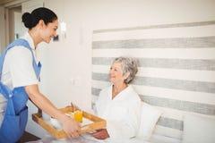 Nurse serving breakfast to senior woman Royalty Free Stock Photos