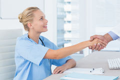 Nurse shaking hand of her colleague Royalty Free Stock Photography