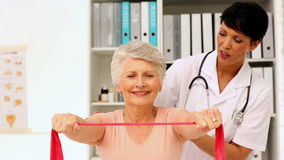 Nurse showing elderly patient how to use resistance band Royalty Free Stock Image
