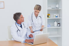 Nurse showing a folder to her colleague. In the office Stock Images