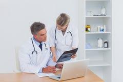 Nurse showing a radiography to her colleague Stock Photos