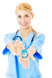 Nurse Showing Toy Alarm Clock Over White Background stock images