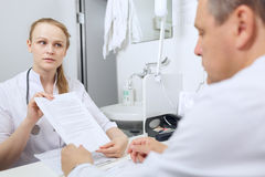 Nurse shows to doctor results of analyses Royalty Free Stock Photo
