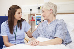 Nurse Sitting By Female Patient's Bed In Hospital Stock Photography