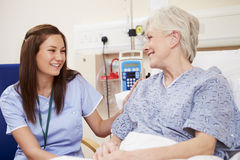 Nurse Sitting By Female Patient's Bed In Hospital Royalty Free Stock Photo