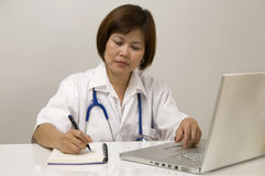 Nurse sitting and writing. Doctor or Nurse sitting at her desk and writing Royalty Free Stock Image