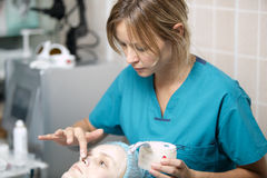 Nurse in a skin clinic applying protective cream Stock Photos