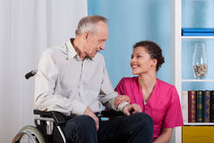 Nurse smiles to sitting in a wheelchair patient Royalty Free Stock Images