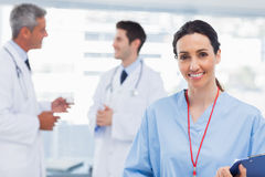 Nurse smiling at camera while doctors are talking together Royalty Free Stock Images