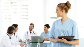 Nurse smiling at camera while staff are talking behind her