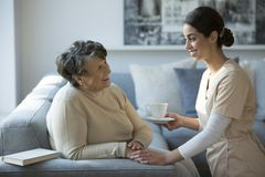 Nurse and smiling grandmother stock photography