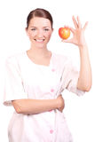 Nurse smiling and holding up an apple Stock Photography