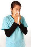 Nurse Sneezing into Tissue. A female nurse sneezing into tissue in order to not spread germs Royalty Free Stock Photos
