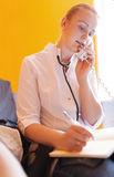 Nurse is speaking on the phone. Nurse is calling on the phone and writes something in notebook Stock Photography
