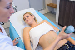 Nurse squirting gel on abdomen patient for scan Stock Photography