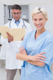 Nurse standing arms crossed while doctor reading reports in clinic Royalty Free Stock Photos