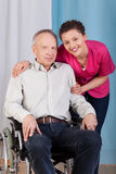 Nurse standing by the disabled in a wheelchair Stock Photography