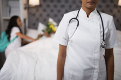 Nurse standing with patient on bed in background Stock Images