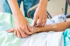Nurse Starting an IV Line. Cropped image of female nurse starting an IV line royalty free stock photography