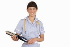 Nurse with stethoscope holding medical file, smiling, front view, portrait, cut out Stock Image