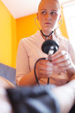 Nurse with stethoscope looks at the patient Stock Photography