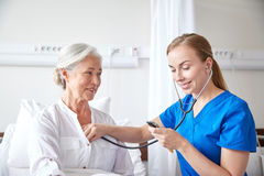 Nurse with stethoscope and senior woman at clinic Stock Photos