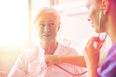 Nurse with stethoscope and senior woman at clinic Royalty Free Stock Photo