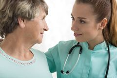 Nurse with stethoscope supporting woman Stock Photo