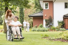 Nurse supporting disabled senior woman in a wheelchair in the ga royalty free stock image