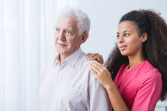 Nurse supporting elder man Stock Images
