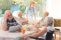 Nurse during daily activities. Nurse supporting elderly people during daily activities in nursing house Royalty Free Stock Images