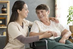 Nurse supporting happy elderly woman Stock Photography