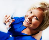 Nurse With Syringe. Mature woman nurse holding up a syringe and smiling royalty free stock photo
