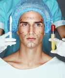 Nurse with syringe and scalpel near the face of the patient Royalty Free Stock Image