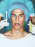 Nurse with syringe and scalpel near the face of the scared patient. Stock Photo