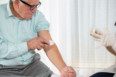 Nurse with syringe is taking blood for test at the doctor office. Female nurse and senior man Stock Photography