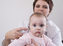 Nurse taking baby's temperature stock photo