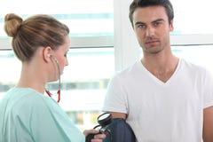 Nurse taking blood pressure Stock Image