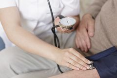 Nurse taking blood pressure Stock Image