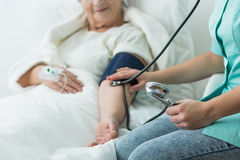 Nurse taking blood pressure Stock Photography