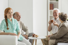 Nurse is taking care of elder people. Nurse is taking care of three elder people during meeting at home Royalty Free Stock Images