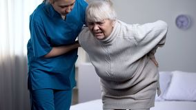 Nurse taking care about old lady suffering from lower back pain, medical center. Stock photo royalty free stock images